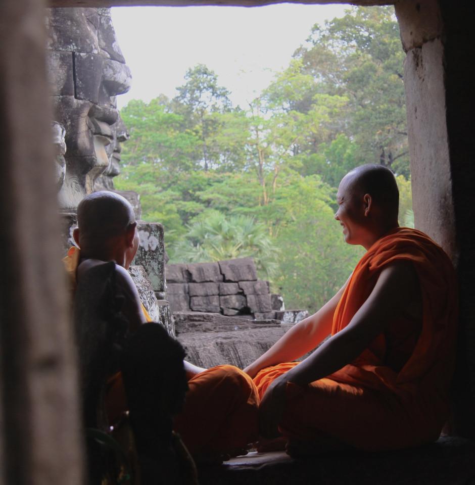 Due monaci osservano le facce in pietra dei Buddha a Angkor Thom